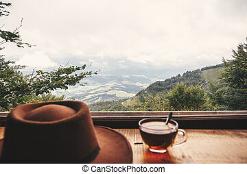 Hot tea in glass cup and hipster hat on background of  beautiful landscape of woods and mountains. View from wooden window on mountain. Space for text. Travel and vacations