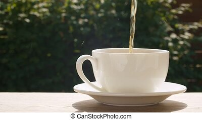 Hot tea pouring into a cup