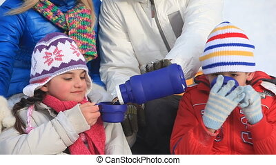 Hot tea - Happy family drinking hot tea outside in winter