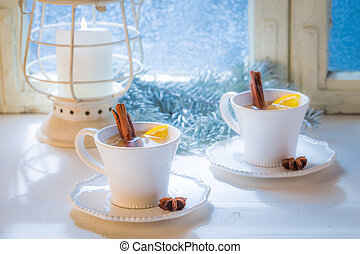 Hot tea with cinnamon for Christmas on white table