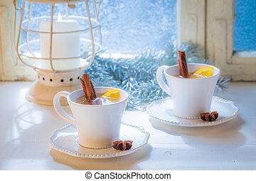 Hot tea with cinnamon for Christmas on white table