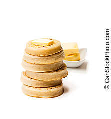 Hot toasted crumpets with butter slice isolated on white