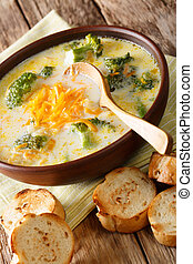 Hot vegetable broccoli cheese soup in a bowl with toasted bread closeup. vertical