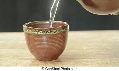 hot water pouring from tea pot to pottery glass