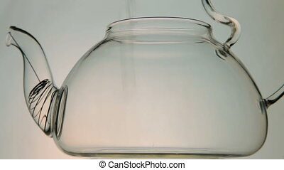 hot water pouring into glass teapot - hot water is poured...