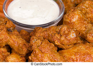 Hot wings with dipping sauce - A close up of crisp; spicy...