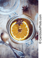 Hot winter drink, herbal tea with orange and star anise in a vintage glass jar on a rustic wooden table