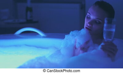 Hot young woman bathing and relaxing with glass of champagne...