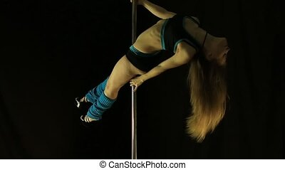 Hot young woman in sexy lingerie performs sensual pole dance. Go-go dancer in nightclub
