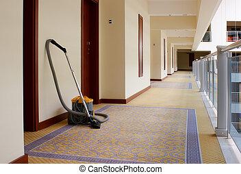 Hotel Corridor - vacuum cleaner stands in the corridor of...