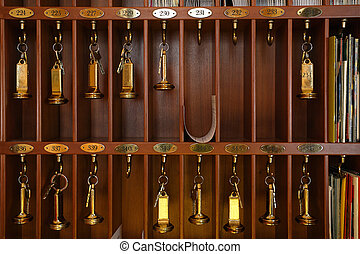 Vintage hotel front desk key rack. Focus on the top row of keys.