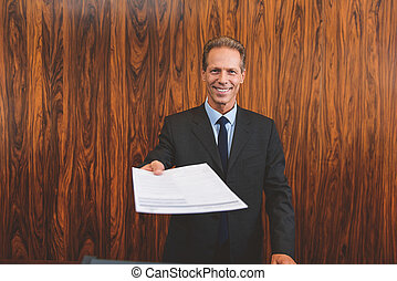 Hotel manager holding papers in hand