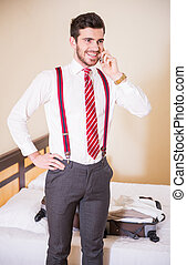Hotel - Handsome businessman is speaking by phone while...
