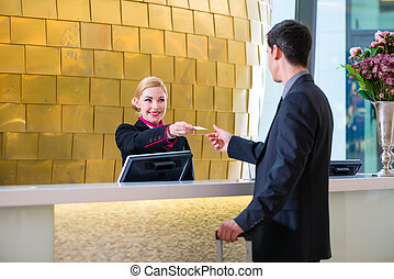 Hotel receptionist check in man giving key card