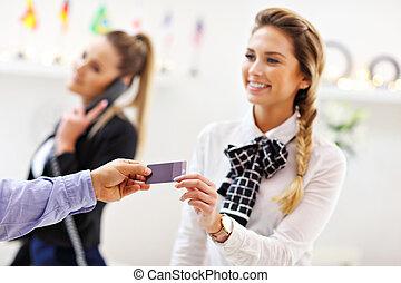 Hotel receptionist giving key card