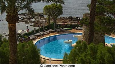 Medium high-angle panoramic still shot of a beautiful circular blue-water swimming pool at an island resort with visitors relaxing, Ibiza Balearic Island, Spain