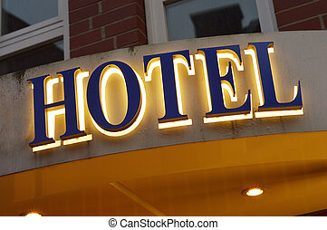 Illuminated hotel sign taken at dusk