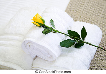 hotel white towel on bed with rose on it