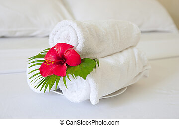 folded towels on bed in hotel room