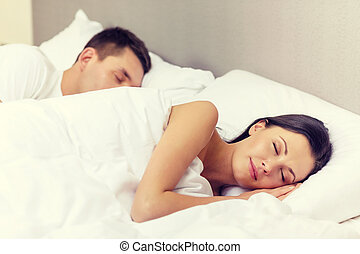 happy couple sleeping in bed - hotel, travel, relationships...