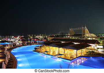 Hotel View at Night - A luxury hotel pool area softly lit at...