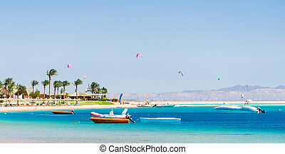 hotel with palm trees on the Red Sea in Egypt Dahab with boats and kite surfers