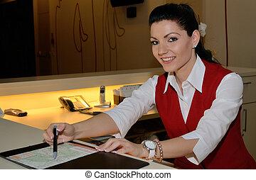 Hotelfachfrau erklaert Landkarte - junge Rezeptionistin...