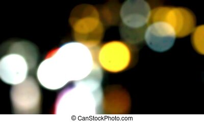 Hotels in mountains at night with lights on background of ripples In sea. Video blurred with bokeh