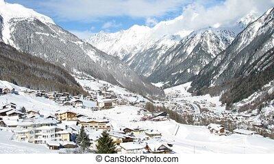 Hotels stand in mountain valley where tourists ski in sunny...