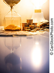 Hourglass and currency on table, Time Investment concept