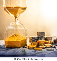 Hourglass and currency on table, Time Investment