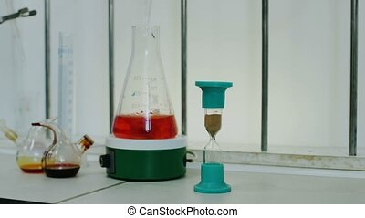 hourglass and flask with liquid in medical laboratory -...