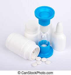 Hourglass and scattered pills from a bottle