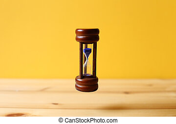 Hourglass floating on wooden table