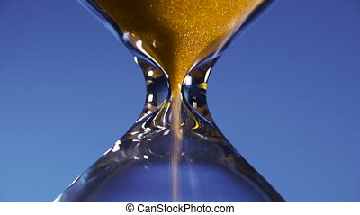 Hourglass golden sand in a transparent flask is poured on a...