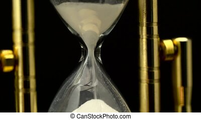 Hourglass is flowing and suddenly stop. Close up. Black...