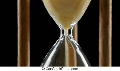 Hourglass is ticking. Yellow sand. Black. Close up - Yellow...