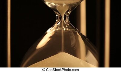 Hourglass. Last grains of sand - Sand falls quickly through...