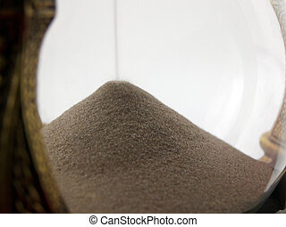 Macro photo of sand falling through an hourglass
