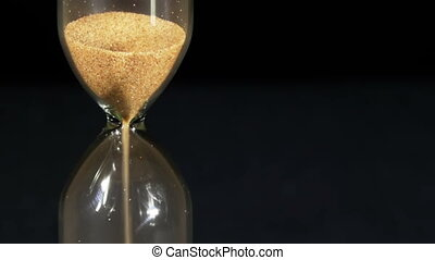 Hourglass on a Black Background, the sand Falls Inside