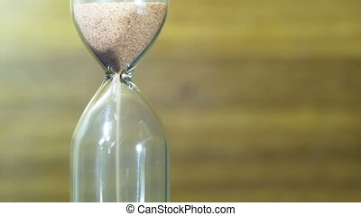 Hourglass on a Wooden Background, the Sand Falls Inside