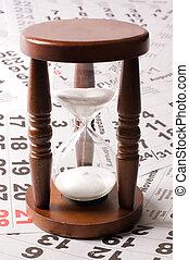 hourglass on calendar sheets