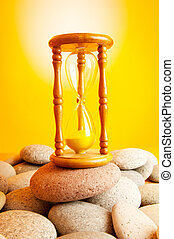 Hourglass on pebbles against gradient