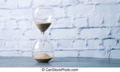 hourglass on table, Sand flowing through the bulb of Sandglass.
