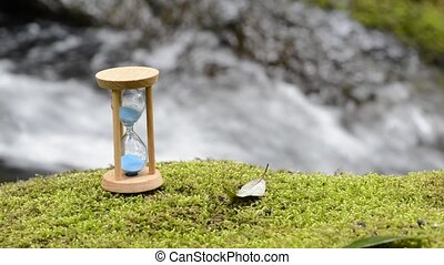 Hourglass on the moss - Hourglass on the green moss in front...