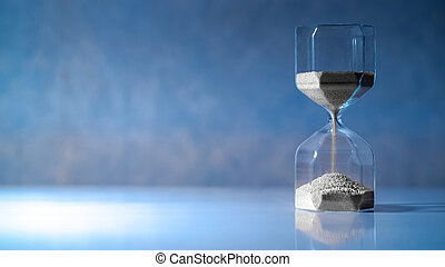 Hourglass on white table, Time passing concept - Sliver sand...