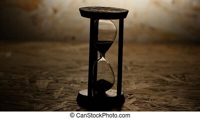 Hourglass with black sand. Clock in wooden base