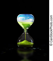 Hourglass with green meadow - An hourglass on a black ...