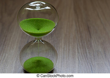 Hourglass with green sand, life time passing concept