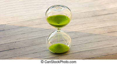 Hourglass with green sand on a wooden background